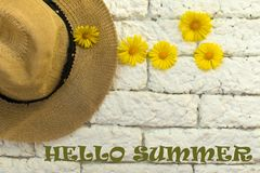 Sign `Hello summer` on a background of white brick wall hat and summer wild flowers stock images