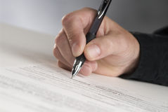 Sign here. Man's hand holding a pen writing his signature Royalty Free Stock Photos