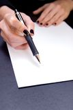 Sign Here. Close-up of hand holding pen pointing to blank document Royalty Free Stock Photos