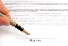 Sign here. Male hand holding fountain pen pointing at signature place Royalty Free Stock Image