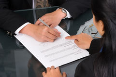 Sign here. A business woman show the place on the document where the director should sign Royalty Free Stock Images