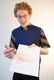 Sign here (mischievous). A nerd enthusiastically signalling you to sign a document (not legible Stock Photos