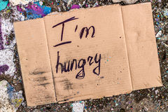 Sign of homeless man on cardboard. Cardboard with request for food donation on the ground stock photography