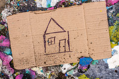 Sign of homeless man on cardboard. Cardboard with request for home on the ground royalty free stock photo
