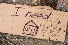 Sign of homeless man on cardboard. Cardboard with request for home on the ground royalty free stock images