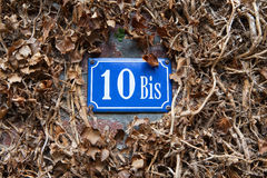 Sign with the house number on a piece of wall. The blue number pointer of the house among the dry leaves Royalty Free Stock Photos