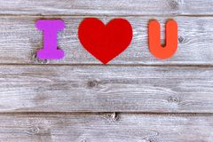 Sign I love you made of colorful letters and felt heart on vintage wooden background with copy space, flat lay.  stock images