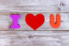 Sign I love you made of colorful letters and felt heart on vintage wooden background, flat lay.  stock photo