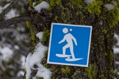 Sign indicated snowshoe trail on moss and snow-covered tree. Blue sign with white graphic nailed to a tree covered with moss and ice, indicates the route of a Royalty Free Stock Photography