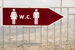 Sign indicating the location of the bathrooms in a mountain area. Red sign with blank symbols indicating the location of the bathrooms in a mountain area with royalty free stock image