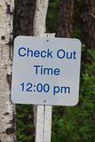 A sign indication check-out time is 12:00 pm.  Stock Photography
