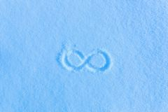 The sign of infinity on the snow. Blue snow, frosty morning. Drawings on the snow stock images