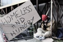 Homeless and hungry sign. Sign with inscription `Homeless and hungry` in metal trolley of a vagrant royalty free stock image