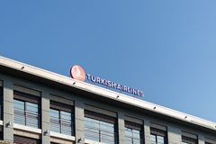 Sign and inscription Turkish Airlines on the roof of the building against the blue sky. International airlines royalty free stock photography