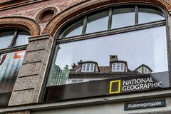 Sign of the international company National Geographic. In a window at kobmagergade, Copenhagen, Denmark, September 21, 2017 Royalty Free Stock Photography