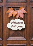 Sign with lettering words Welcome Autumn decorated with two orange maple leaves hanging on dark wooden entrance door. stock image