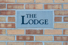 Sign 'The Lodge' on a brick wall Royalty Free Stock Photos