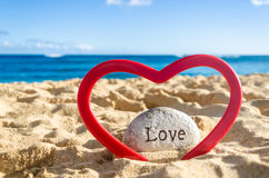 Sign Love with heart on the sandy beach Royalty Free Stock Image