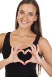 The sign of love and kindness. Happy brunette woman in black t-shirt, isolated on white background Royalty Free Stock Photography