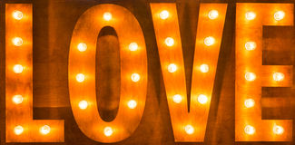 Sign love light bulbs on wooden background. Royalty Free Stock Image