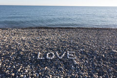 The sign Love made from white pebbles. On pebble beach on the sea Stock Images