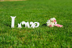 Sign of Love and wedding bouquet on a green lawn. Royalty Free Stock Photography