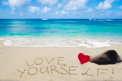 Sign. Love yourself with heart on the sandy beach by the ocean Stock Photos