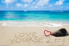Sign. Love yourself with heart on the sandy beach by the ocean Royalty Free Stock Images