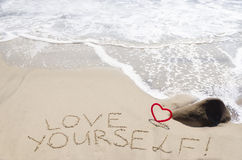 Sign. Love yourself with heart on the sandy beach by the ocean Royalty Free Stock Photos