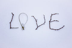 Sign made of wood in the snow. St. Valentine`s Day. red glass heart on snow Royalty Free Stock Photos
