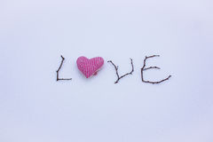 Sign made of wood in the snow. St. Valentine`s Day. red heart on snow Royalty Free Stock Photos