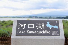 Information sign map stone Lake Kawaguchiko, mountains, Japan. Sign and map of Lake Kawaguchiko on a stone along the laker water and mountain views, near Mount stock photos