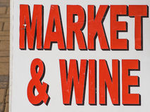 Sign of market & wine. Bright red letter saying market & wine on not so new white background board standing on brick walkway Royalty Free Stock Images