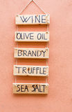 Sign marking the sale of typical products written: wine, olive oil, brandy, tratufo, sea salt.  royalty free stock image