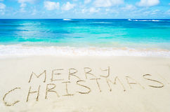Sign Marry Christmas! on the sandy beach. By the ocean - holiday concept Stock Image