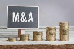 Sign Mergers and Acquisitions with growth coin stacks Royalty Free Stock Photo