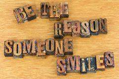 Be the reason someone smiles letterpress. Sign message be the reason someone smiles love letterpress block letters words greeting wood background Royalty Free Stock Images