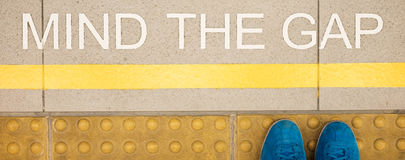 The sign Mind the gap painted on train station's platform edge stock photography