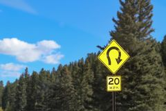 Sign beside mountain road in front of evergreen trees warning of extreme curve and speed limit of 20 mph - selective focus.  stock images
