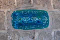A sign with the name of the street in Hebrew - Lane of the sign of the zodiac Pisces in on old city Yafo in Tel Aviv-Yafo in Israe. Tel Aviv-Yafo, Israel stock photography