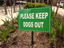 Sign, Please Keep Dogs Out. This sign near City Hall in Philadelphia tells dog owners to please keep their pet out of the flowerbeds. This photo was taken in royalty free stock photos