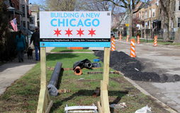Sign near road work in Chicago. Sign announces road work on a residential Chicago street. A family and American flag can be seen in the background Stock Images