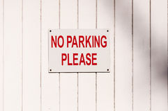 Sign 'No Parking Please' mounted on a painted shadowed wooden su Stock Photos