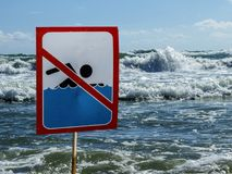 The Sign no swim on the beach amid the big waves of the ocean royalty free stock photos