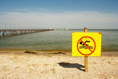 Sign no swimming on the background of the sea and pier. A sign on a yellow background Stock Photography