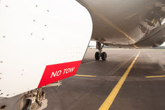 Sign NO TOW on undercarriage of airplane - jetplane waiting on r. Sign NO TOW on undercarriage of airplane while waiting on runway Stock Photography