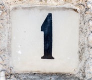 A sign with a number one on an old whitewashed wall. Close up Stock Photography