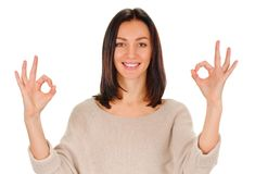 Young lady indicating ok sign. Young woman shows sign and symbol ok on white background Royalty Free Stock Images