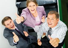 Sign of okay. Portrait of business people giving the thumbs-up sign Royalty Free Stock Images