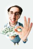 Sign of okay. Wide angle of young man with dollars showing sign of okay and looking at camera Royalty Free Stock Image